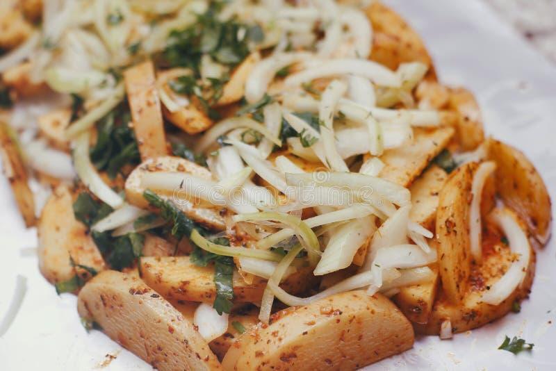 Ακατέργαστη πατάτα που τεμαχίζεται σε ένα φύλλο αλουμινίου ψησίματος Προετοιμασμένος για το μαγείρεμα με τα καρυκεύματα, λαχανικά στοκ φωτογραφίες με δικαίωμα ελεύθερης χρήσης