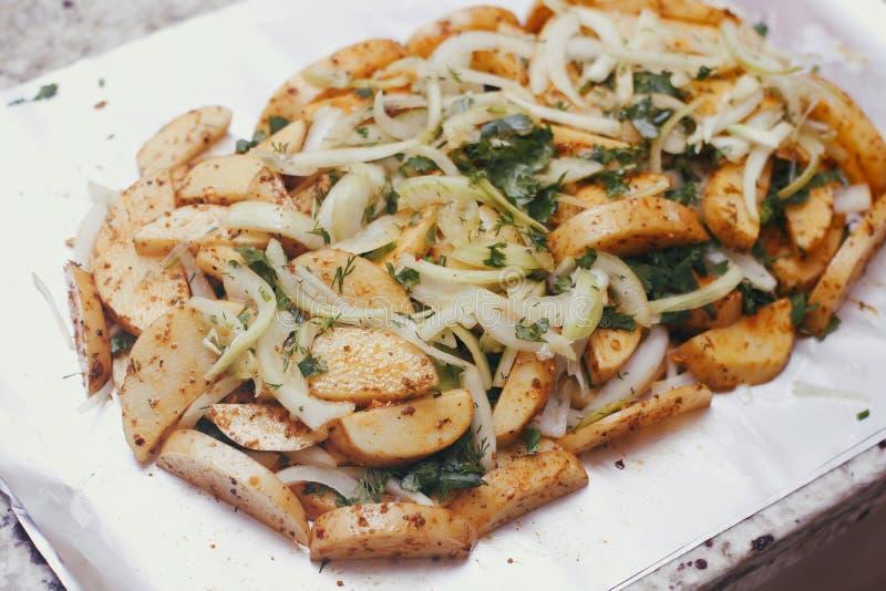 Ακατέργαστη πατάτα που τεμαχίζεται σε ένα φύλλο αλουμινίου ψησίματος Προετοιμασμένος για το μαγείρεμα με τα καρυκεύματα, λαχανικά στοκ εικόνες