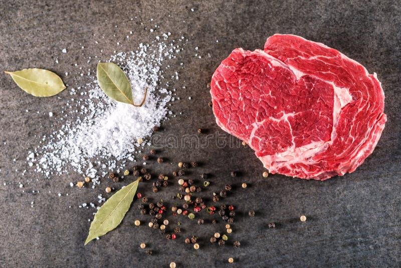 Ακατέργαστη λωρίδα μπριζόλας βόειου κρέατος με τα συστατικά όπως τα φύλλα αλατιού, πιπεριών και κόλπων θάλασσας στο μαύρο πίνακα, στοκ φωτογραφία με δικαίωμα ελεύθερης χρήσης
