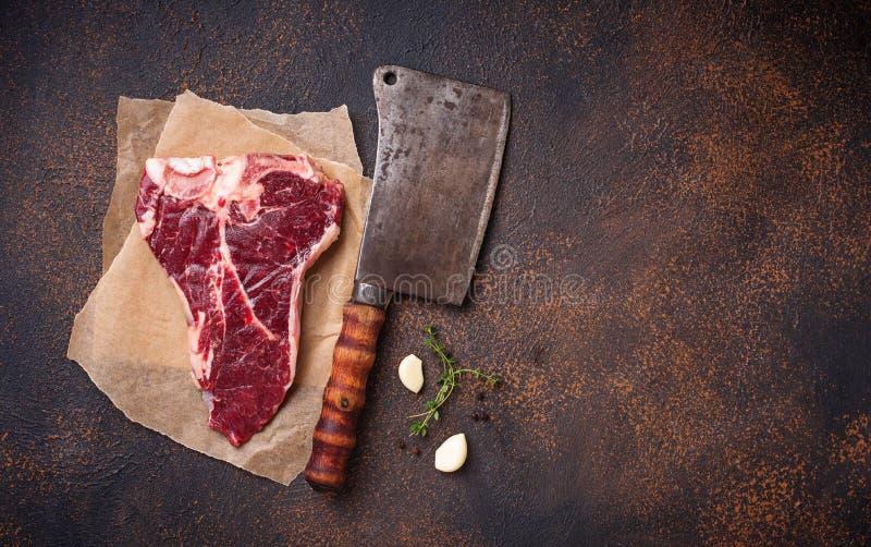Ακατέργαστη T-bone μπριζόλα με το μαχαίρι χασάπηδων στοκ φωτογραφίες