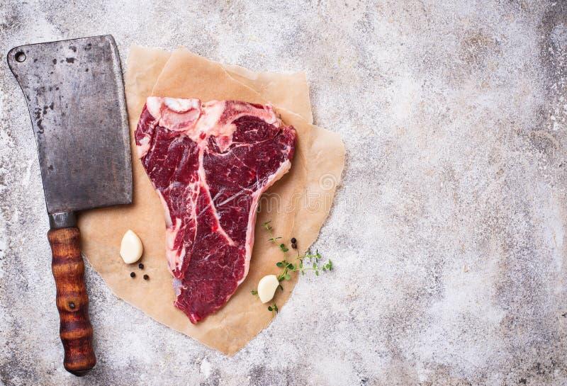 Ακατέργαστη T-bone μπριζόλα με το μαχαίρι χασάπηδων στοκ εικόνα