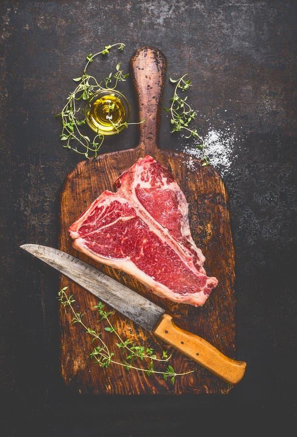Ακατέργαστη T-bone μπριζόλα για τη σχάρα ή BBQ με τα φρέσκα χορτάρια και μαχαίρι πετρελαίου και κουζινών στο σκοτεινό ηλικίας τέμ στοκ εικόνες με δικαίωμα ελεύθερης χρήσης