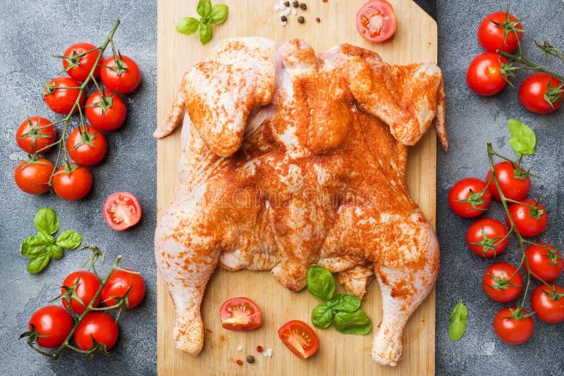 Ακατέργαστος καπνός κοτόπουλου σε έναν ξύλινο πίνακα με τα καρυκεύματα και τα λαχανικά στοκ εικόνα