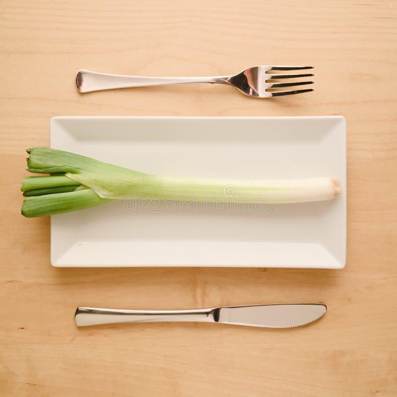 Ακατέργαστο άκοπο κρεμμύδι άνοιξη διατροφής χαμηλός-εξαερωτήρων Vegan στο ορθογώνιο πιάτο στοκ εικόνες