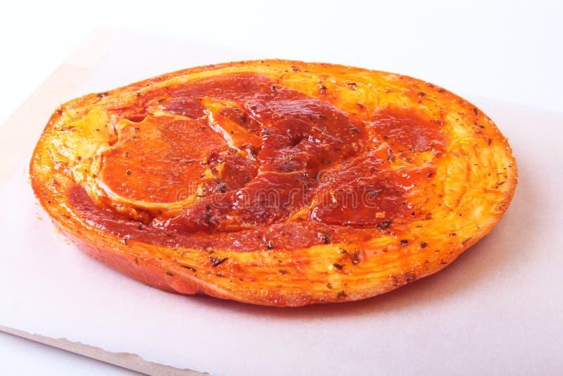 Ακατέργαστο ζαμπόν χοιρινού κρέατος με τα καρυκεύματα και τα φύλλα μαϊντανού έτοιμα για BBQ το ψήσιμο στη σχάρα που απομονώνεται  στοκ εικόνα