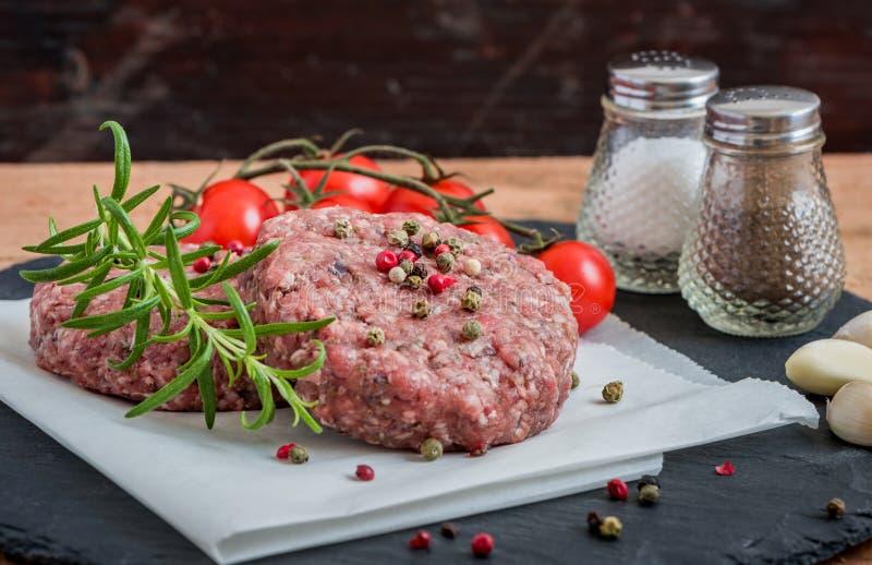 Ακατέργαστο κομματιασμένο κρέας χάμπουργκερ με το χορτάρι και το καρύκευμα στοκ εικόνες