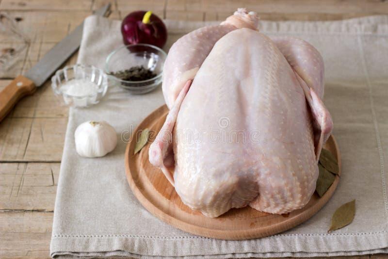 Ακατέργαστο κοτόπουλο σε έναν ξύλινο πίνακα με τα καρυκεύματα και τα λαχανικά στοκ φωτογραφίες