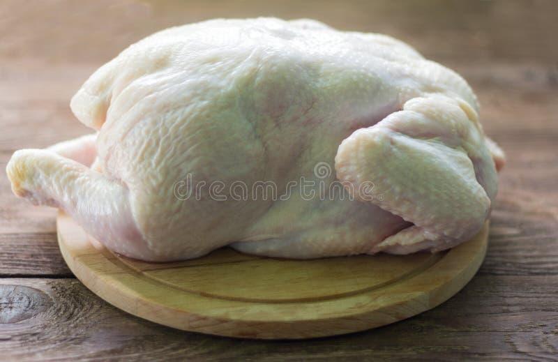 ακατέργαστο κοτόπουλο, σφάγιο κοτόπουλου σχαρών στον τέμνοντα πίνακα στοκ εικόνες