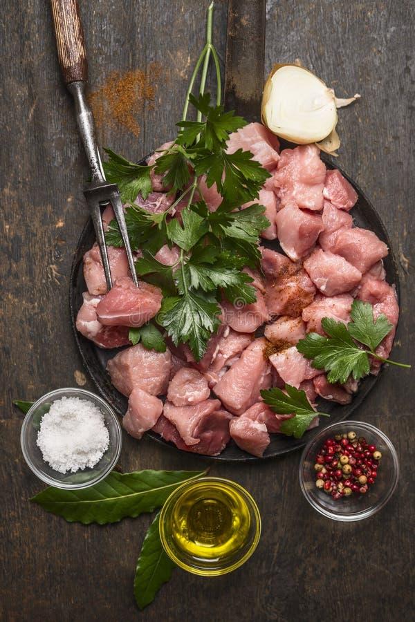Ακατέργαστο κρέας για Goulash την προετοιμασία με το έλαιο και τα φρέσκα χορτάρια και καρυκεύματα στο αγροτικό ξύλινο υπόβαθρο στοκ εικόνες με δικαίωμα ελεύθερης χρήσης