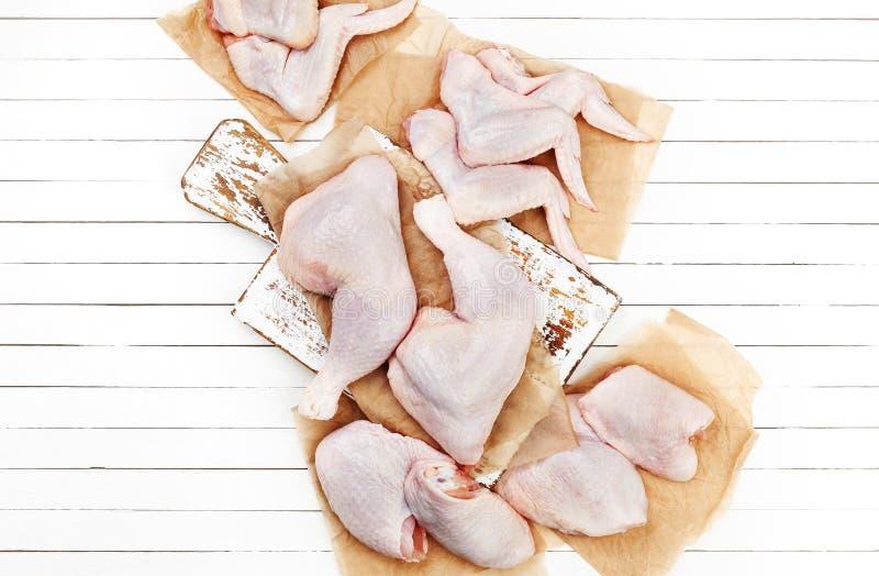 Ακατέργαστο κρέας κοτόπουλου στον τέμνοντα πίνακα στο άσπρο ξύλινο υπόβαθρο Τοπ όψη στοκ φωτογραφία με δικαίωμα ελεύθερης χρήσης