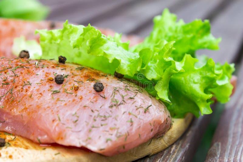 Ακατέργαστο κρέας με τα καρυκεύματα και τα φρέσκα φύλλα σαλάτας σε ένα παλαιό εκλεκτής ποιότητας ξύλινο υπόβαθρο στοκ εικόνες