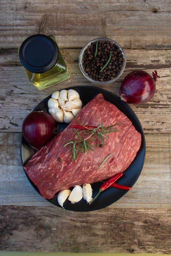 Ακατέργαστο κρέας, μπριζόλα βόειου κρέατος στον αγροτικό ξύλινο πίνακα με τα καρυκεύματα στοκ φωτογραφία