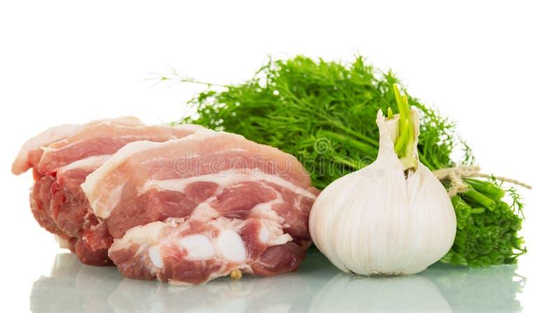 Ακατέργαστο κρέας, σκόρδο και άνηθος χοιρινού κρέατος κομματιού που απομονώνονται στο λευκό στοκ φωτογραφία