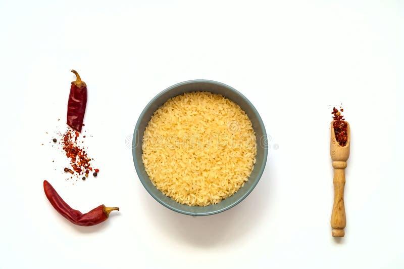 Ακατέργαστο ρύζι στο μπλε κύπελλο και καρυκεύματα που απομονώνονται στο άσπρο υπόβαθρο Η έννοια των χορτοφάγων τροφίμων, υγιεινή  στοκ εικόνα με δικαίωμα ελεύθερης χρήσης