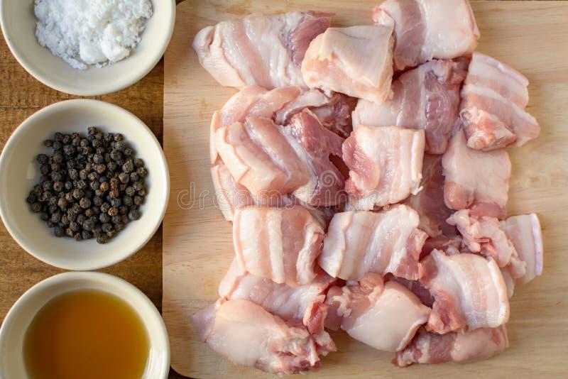 Ακατέργαστο χοιρινό κρέας σε ένα τέμνον ξύλινο επιτραπέζιο υπόβαθρο πινάκων στοκ εικόνες