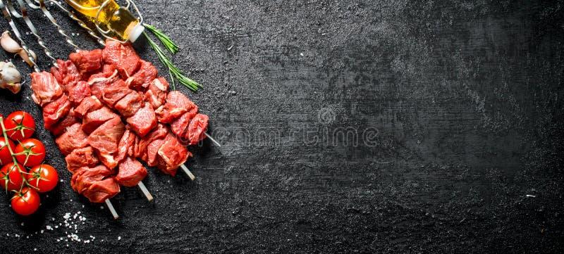 Ακατέργαστο kebab με τις ντομάτες σε έναν κλάδο, ένα έλαιο και ένα σκόρδο στοκ φωτογραφία