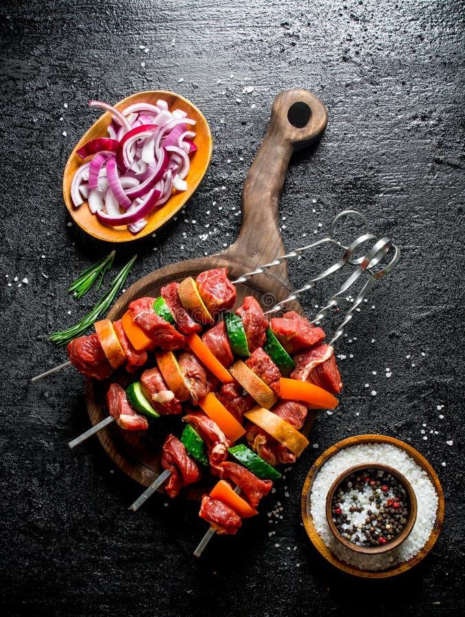 Ακατέργαστο kebab σε έναν πίνακα κοπής με τα τεμαχισμένα κρεμμύδια και τα καρυκεύματα στα κύπελλα στοκ φωτογραφίες με δικαίωμα ελεύθερης χρήσης