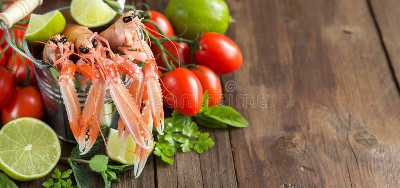Ακατέργαστο langoustine σε έναν κάδο και τα λαχανικά στοκ φωτογραφίες