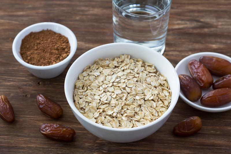 Ακατέργαστο oatmeal σε ένα άσπρο κύπελλο, τα φρούτα ημερομηνιών, το κακάο και ένα ποτήρι του νερού, συστατικά για το εύγευστο υγι στοκ φωτογραφία με δικαίωμα ελεύθερης χρήσης