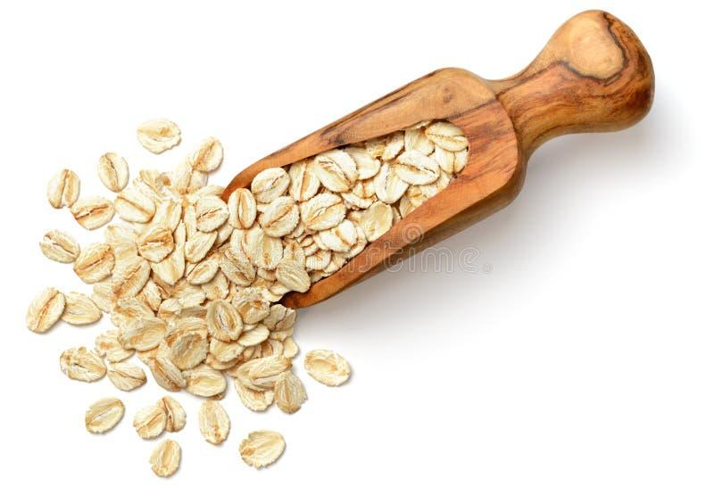 Ακατέργαστο oatmeal στην ξύλινη σέσουλα, που απομονώνεται στην άσπρη, τοπ άποψη στοκ εικόνα
