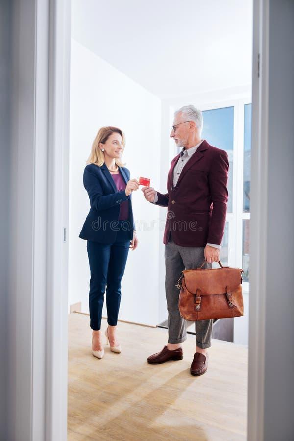 Ακμάζων επιχειρηματίας που δίνει στην κάρτα ονόματός του τον ελκυστικό νέο συνεργάτη του στοκ φωτογραφία με δικαίωμα ελεύθερης χρήσης