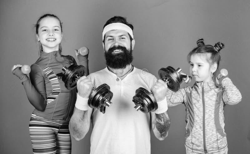 Ακολουθήστε τον πατέρα Χαριτωμένα παιδιά κοριτσιών που ασκούν με τους αλτήρες με τον μπαμπά r Τα παιδιά επαναλαμβάνουν στοκ εικόνα
