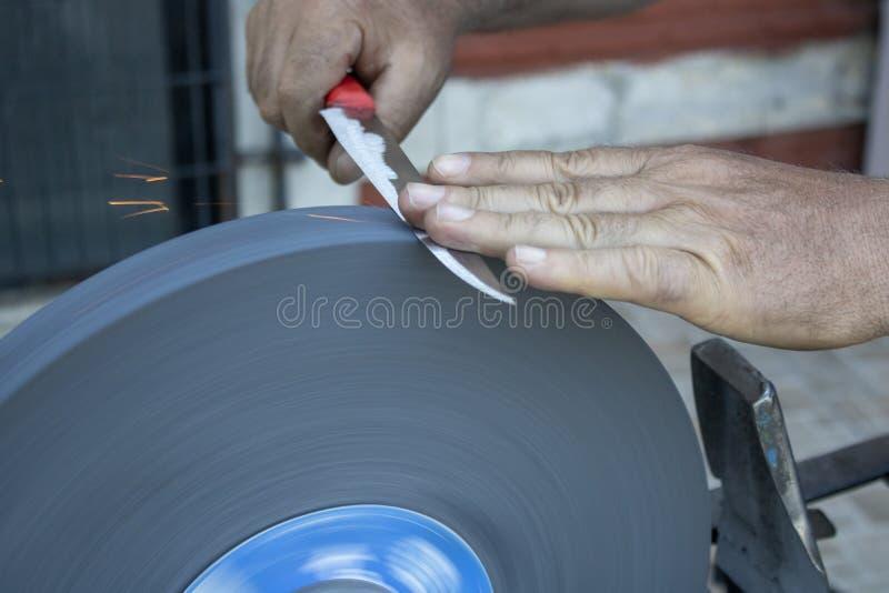 Ακονίζοντας χέρι μαχαιριών και στρώνοντας με άμμο κινηματογράφηση σε πρώτο πλάνο μηχανών στοκ φωτογραφία με δικαίωμα ελεύθερης χρήσης