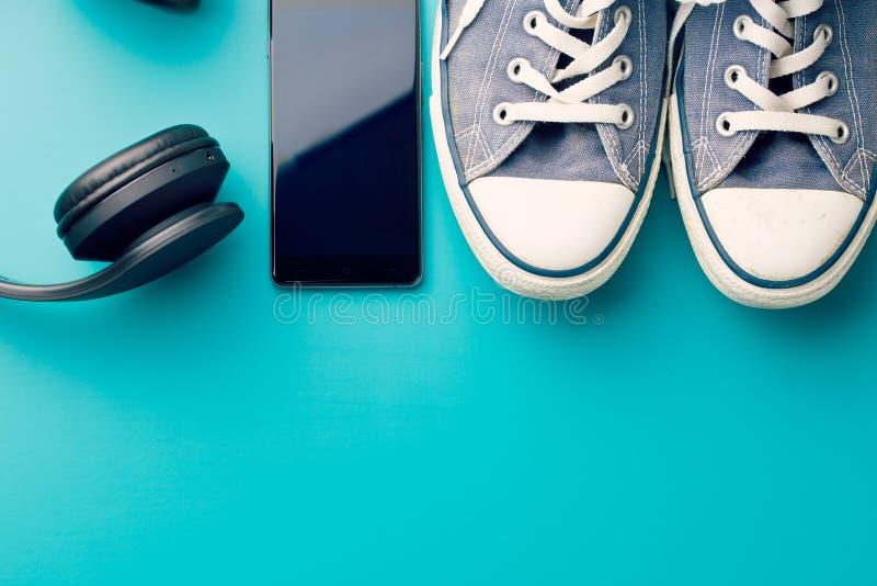 Ακουστικά, έξυπνα τηλέφωνο και πάνινα παπούτσια στοκ εικόνες