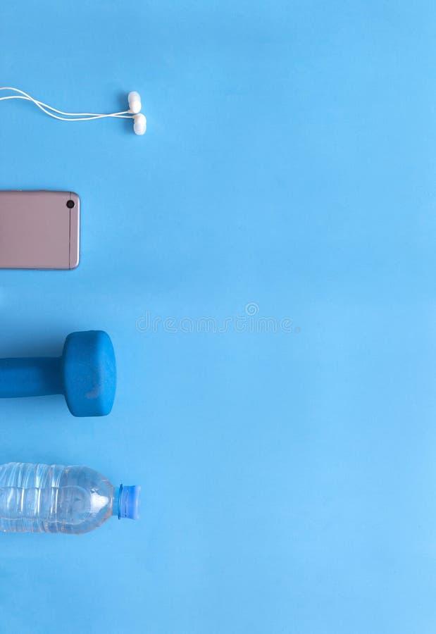 ακουστικά, αλτήρας, μπουκάλι νερό, τηλέφωνο, συσκευή στο μπλε backgr στοκ φωτογραφία με δικαίωμα ελεύθερης χρήσης