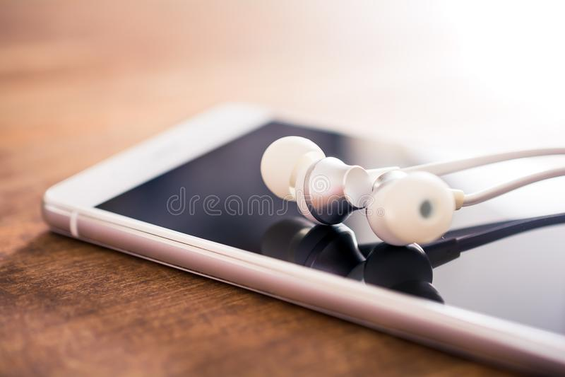 Ακουστικά -αυτιών που βρίσκονται πάνω από ένα άσπρο Smartphone σε έναν ξύλινο πίνακα στοκ εικόνες με δικαίωμα ελεύθερης χρήσης