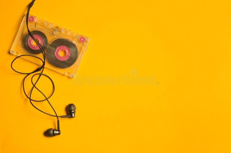 Ακουστικά και αναδρομική κασέτα στο κίτρινο υπόβαθρο διάστημα αντιγράφων στοκ φωτογραφία