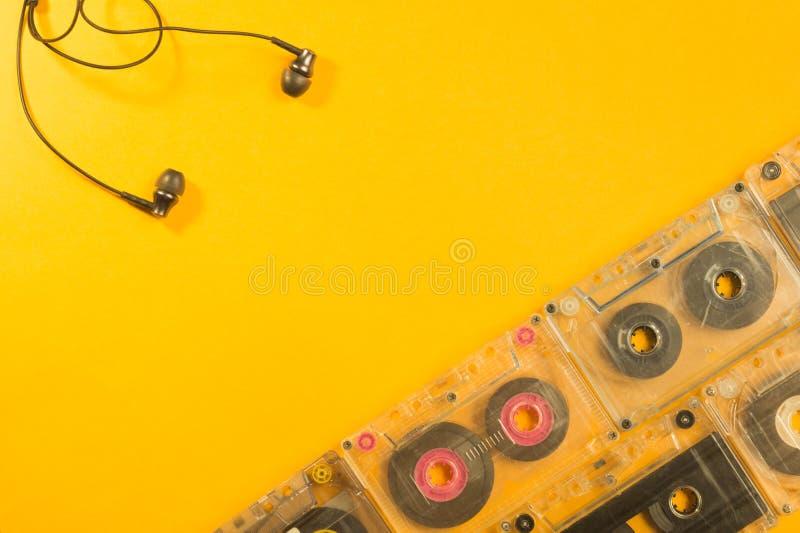 Ακουστικά και αναδρομική κασέτα στο κίτρινο υπόβαθρο διάστημα αντιγράφων στοκ φωτογραφία με δικαίωμα ελεύθερης χρήσης