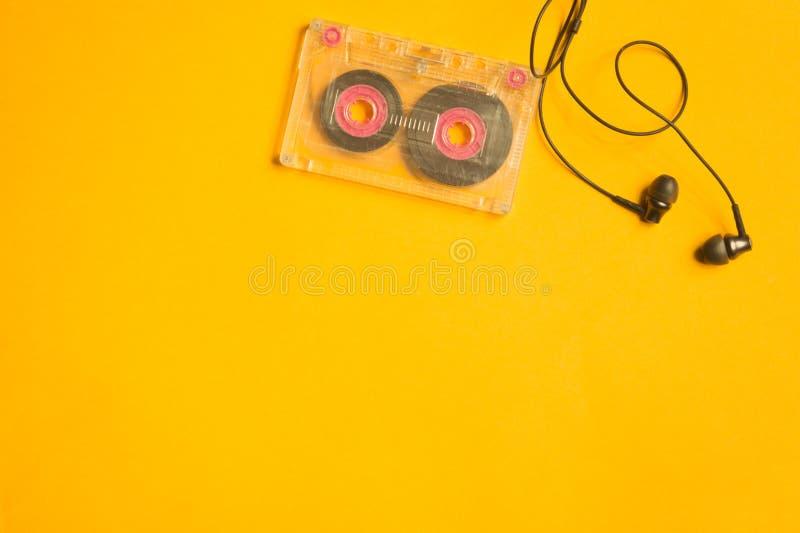 Ακουστικά και αναδρομική κασέτα στο κίτρινο υπόβαθρο διάστημα αντιγράφων στοκ εικόνα