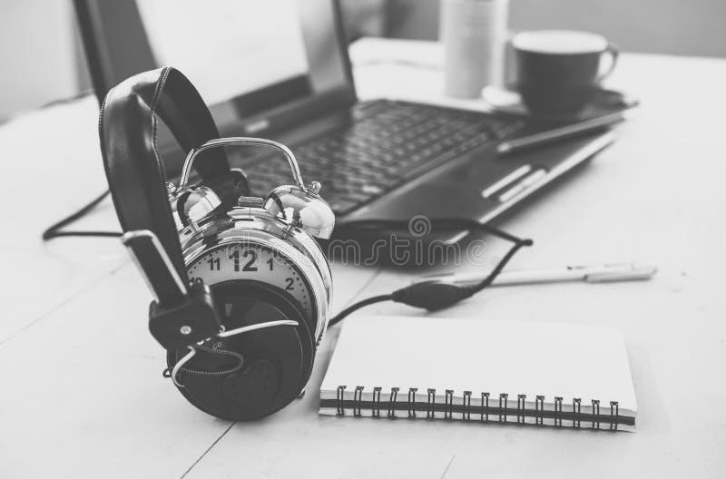 ακουστικά και ξυπνητήρι στον πίνακα εργασίας Η εκπαίδευση ή χαλαρώνει con στοκ εικόνα