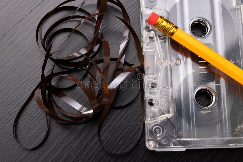 Ακουστικά κασέτα και μολύβι σε έναν μαύρο πίνακα Παλαιός μαγνητικός μεταφορέας στοιχείων στοκ εικόνες