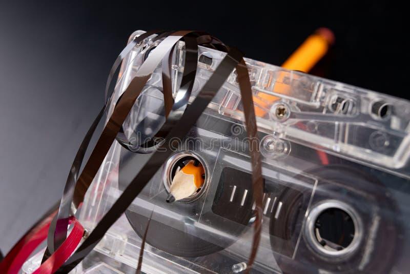 Ακουστικά κασέτα και μολύβι σε έναν μαύρο πίνακα Παλαιός μαγνητικός μεταφορέας στοιχείων στοκ φωτογραφίες