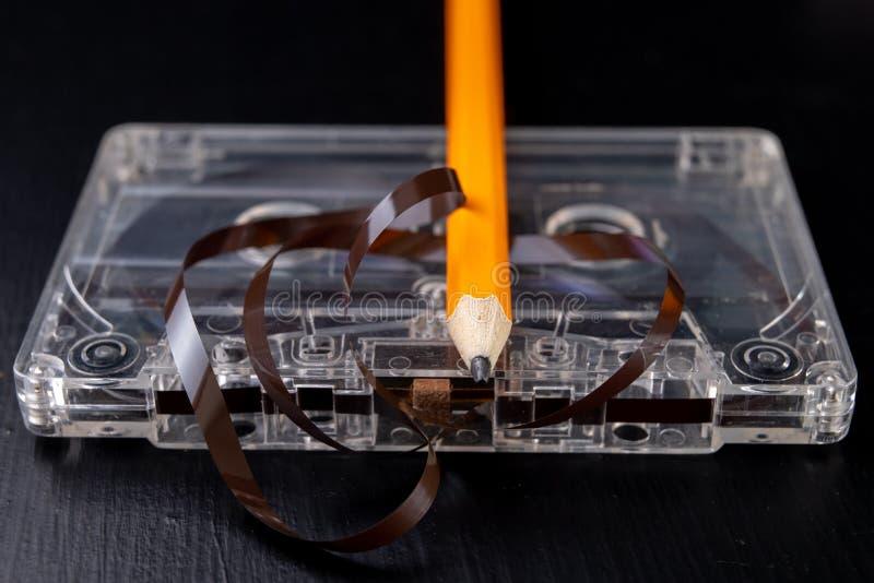 Ακουστικά κασέτα και μολύβι σε έναν μαύρο πίνακα Παλαιός μαγνητικός μεταφορέας στοιχείων στοκ φωτογραφία