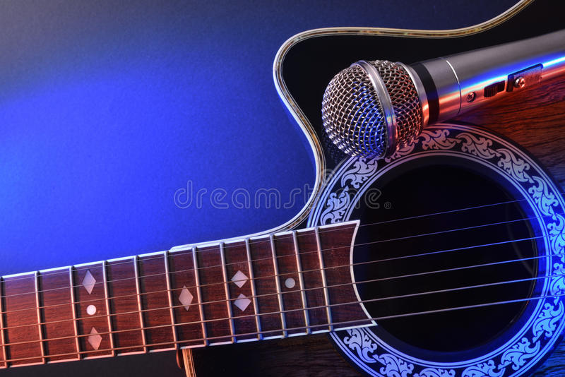 Ακουστικά κιθάρα και μικρόφωνο που απομονώνονται με τα κόκκινα και μπλε φω'τα στοκ εικόνες