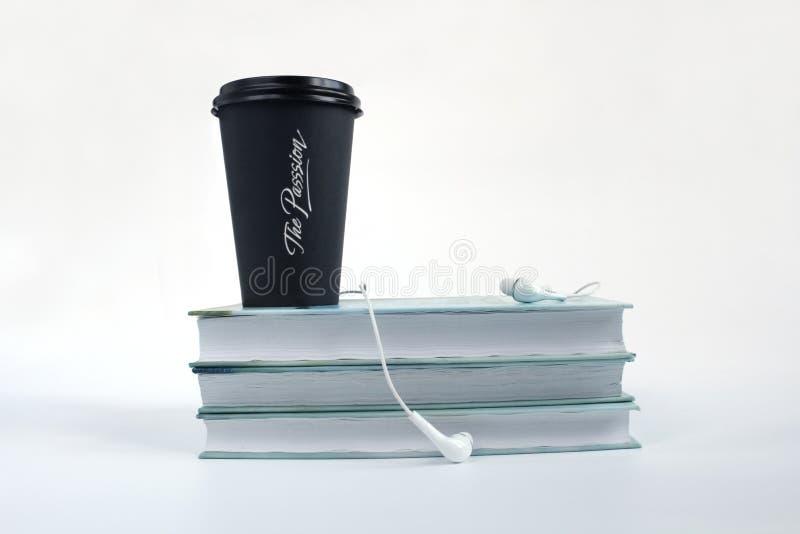 Ακουστική έννοια βιβλίων Ακουστικά, μαύροι φλιτζάνι του καφέ και σωρός των βιβλίων στο άσπρο υπόβαθρο r στοκ φωτογραφίες