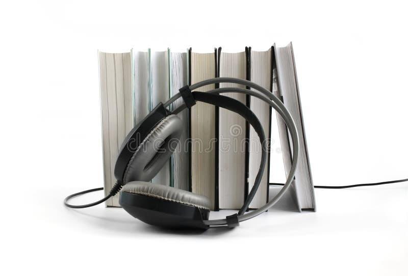 Ακουστική έννοια βιβλίων Μεγάλα μαύρα ακουστικά κοντά στο σωρό των βιβλίων στο άσπρο υπόβαθρο r στοκ εικόνα