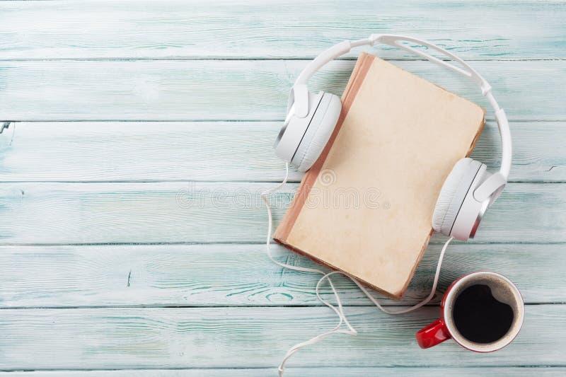 Ακουστική έννοια βιβλίων Ακουστικά, καφές και βιβλίο στοκ φωτογραφίες