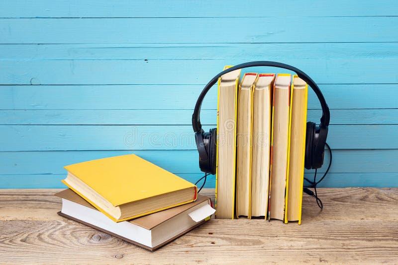Ακουστική έννοια βιβλίων, βιβλίο και ακουστικά πέρα από το ξύλινο υπόβαθρο στοκ εικόνα με δικαίωμα ελεύθερης χρήσης