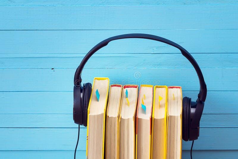 Ακουστική έννοια βιβλίων, βιβλίο και ακουστικά πέρα από το ξύλινο υπόβαθρο στοκ φωτογραφία