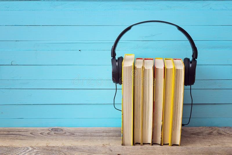 Ακουστική έννοια βιβλίων, κίτρινα βιβλία και ακουστικά πέρα από το μπλε backgr στοκ εικόνες