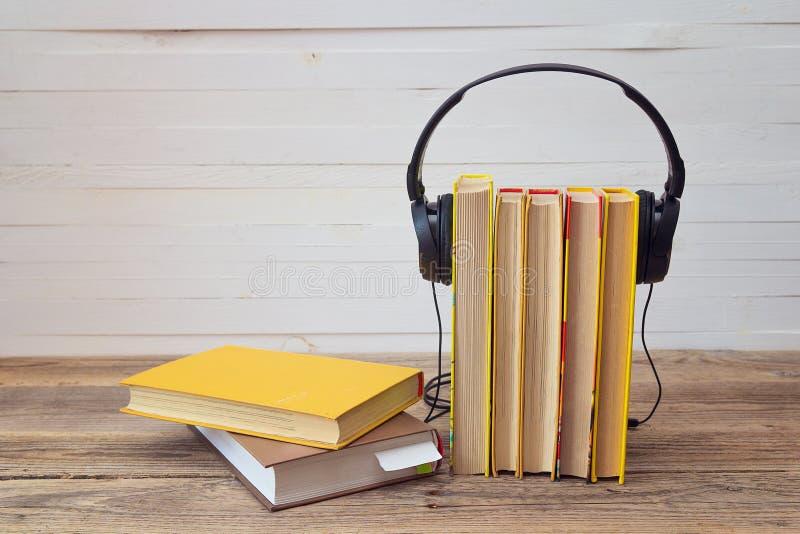 Ακουστική έννοια βιβλίων, κίτρινα βιβλία και ακουστικά πέρα από το άσπρο backg στοκ εικόνες