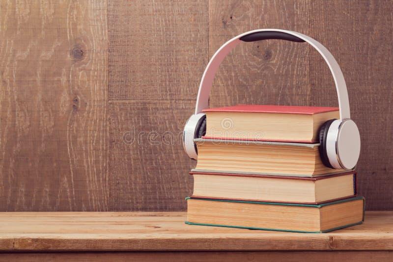 Ακουστική έννοια βιβλίων με το σωρό του παλαιών βιβλίου και των ακουστικών στον ξύλινο πίνακα στοκ εικόνες