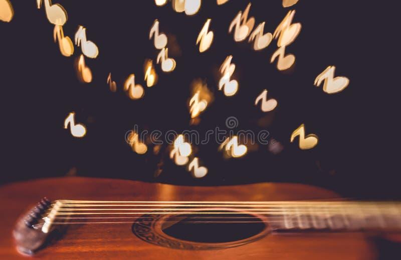 Ακουστική κιθάρα με τη μουσική νότα bokeh στο υπόβαθρο στοκ εικόνα