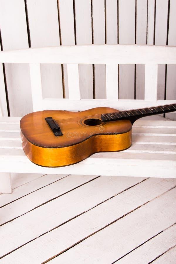 Ακουστική κιθάρα με το αφηρημένο ξύλινο υπόβαθρο στοκ εικόνα