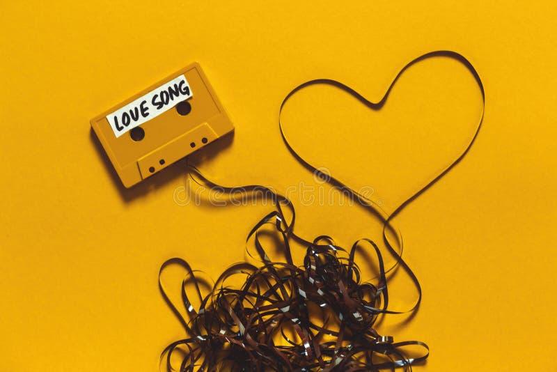 Ακουστική ταινία κασετών με το ερωτικό τραγούδι επιγραφής και καρδιά σε ένα κίτρινο υπόβαθρο Αναδρομική ρωμανική έννοια τεχνολογί στοκ φωτογραφίες με δικαίωμα ελεύθερης χρήσης