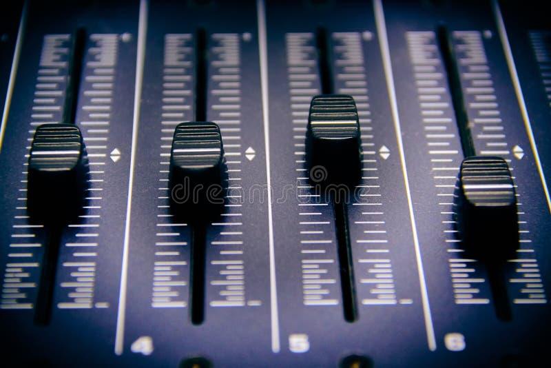 Ακουστικός αναμίκτης, αναμιγνύοντας τους ελέγχους γραφείων και fader, τη μουσική που αναμιγνύει την κονσόλα με τα υποβιβασμένα απ στοκ εικόνα